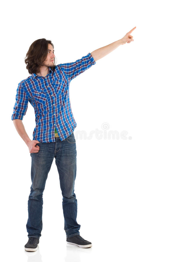 Ung man som bort pekar och ser fotografering för bildbyråer