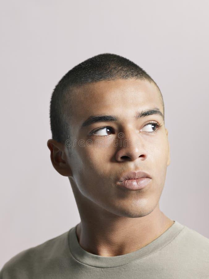 Ung man som bort ser royaltyfri fotografi