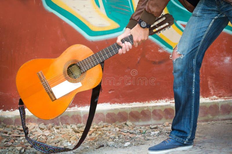 Ung man som bryter en gitarr på golvet arkivfoton