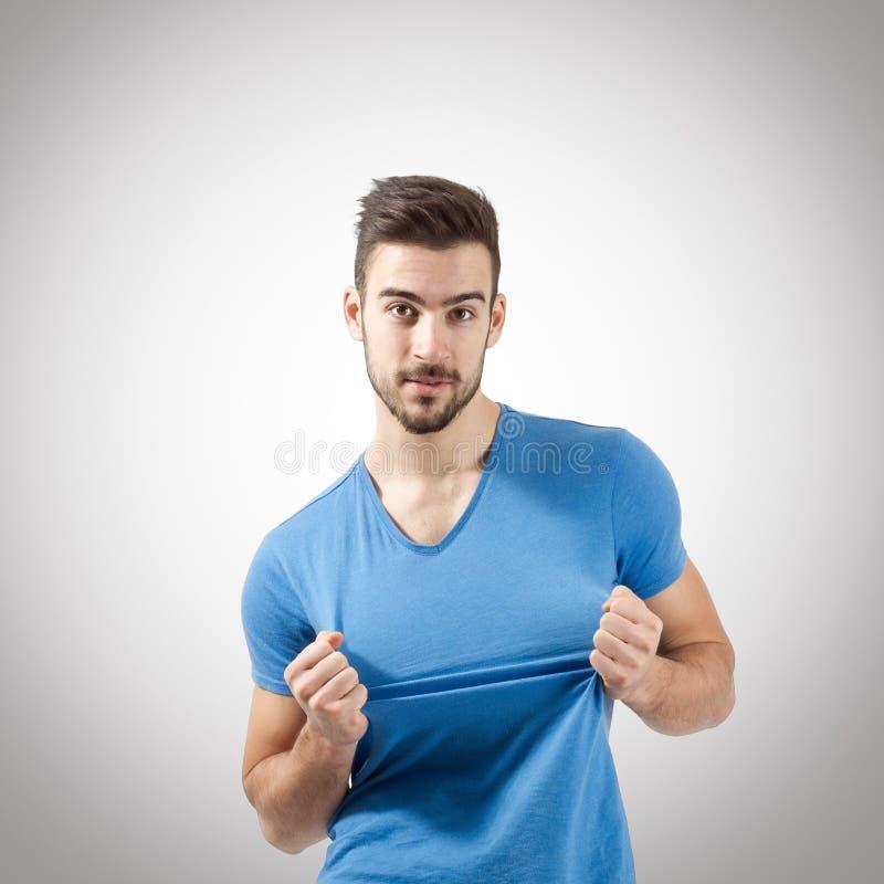 Ung man som drar denskjorta ståenden fotografering för bildbyråer