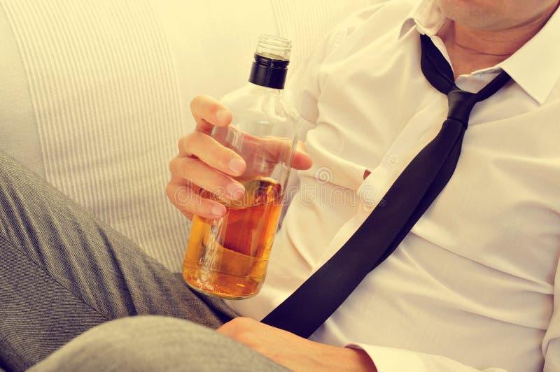 Ung man som dricker alkohol från en flaska royaltyfria bilder