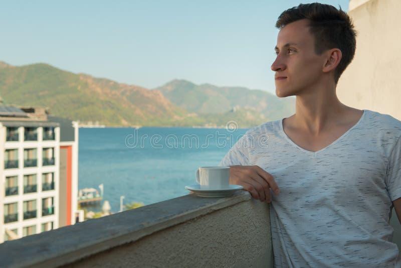 Ung man som dricker doftande kaffe, medan stå på balkongen av hennes rum på hotellet arkivfoto