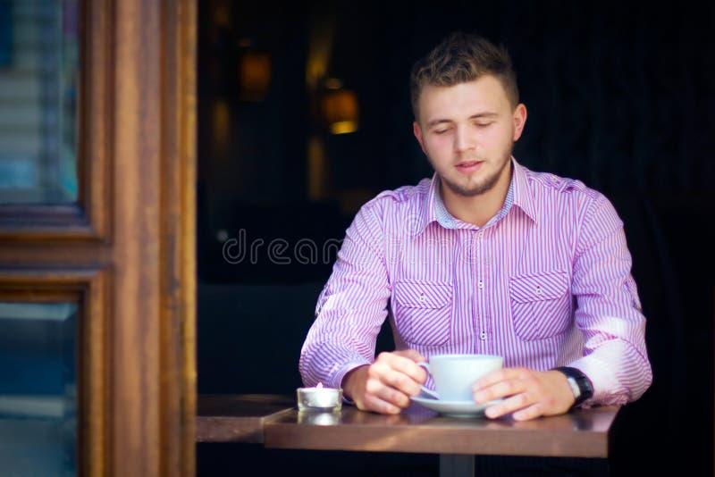 Ung man som dricker kaffe fotografering för bildbyråer
