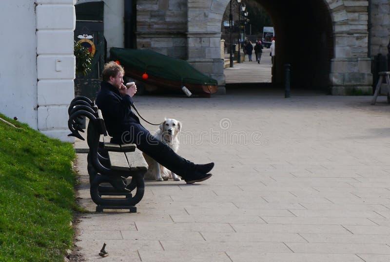Ung man som dricker kaffe på en bänk i större London UK royaltyfri fotografi