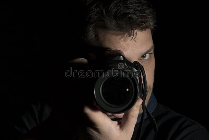 Ung man som en fotografstående som isoleras på svart arkivbilder