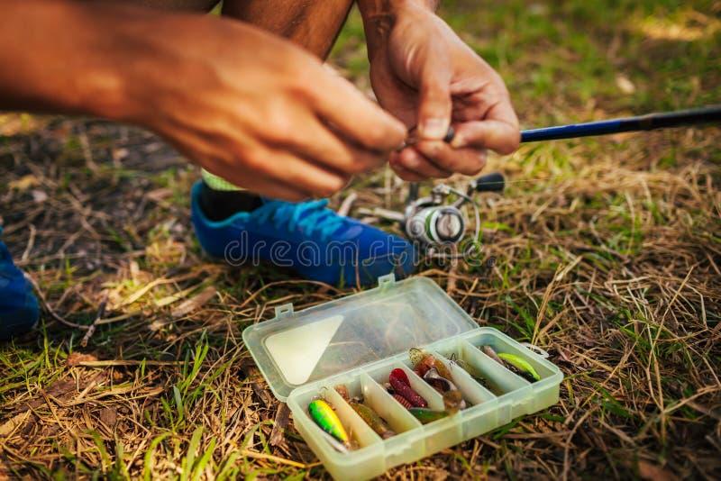 Ung man som fäster bete till kroken av snurret lyckat redskap för stor fiskespinner Mannen väljer drag i fiskekugghjulask arkivfoton