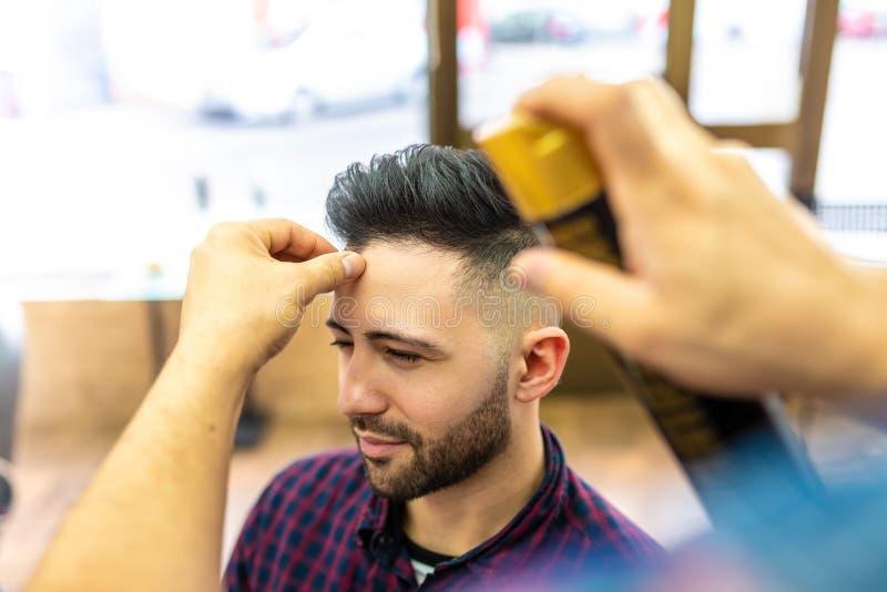 Ung man som får en frisyr i en frisersalong royaltyfria foton