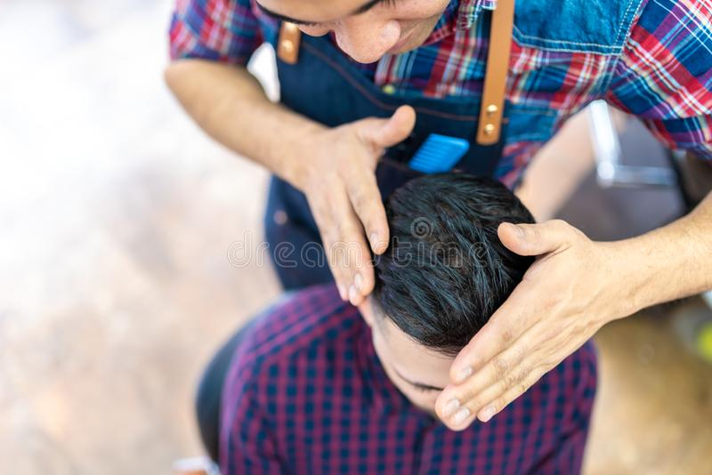 Ung man som får en frisyr i en frisersalong royaltyfri foto