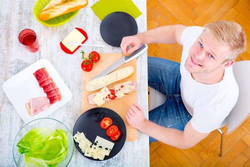 Ung man som förbereder en smörgås fotografering för bildbyråer
