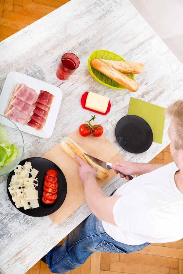 Ung man som förbereder en smörgås royaltyfri fotografi
