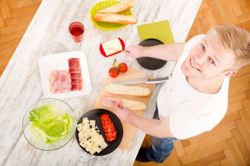 Ung man som förbereder en smörgås royaltyfri bild