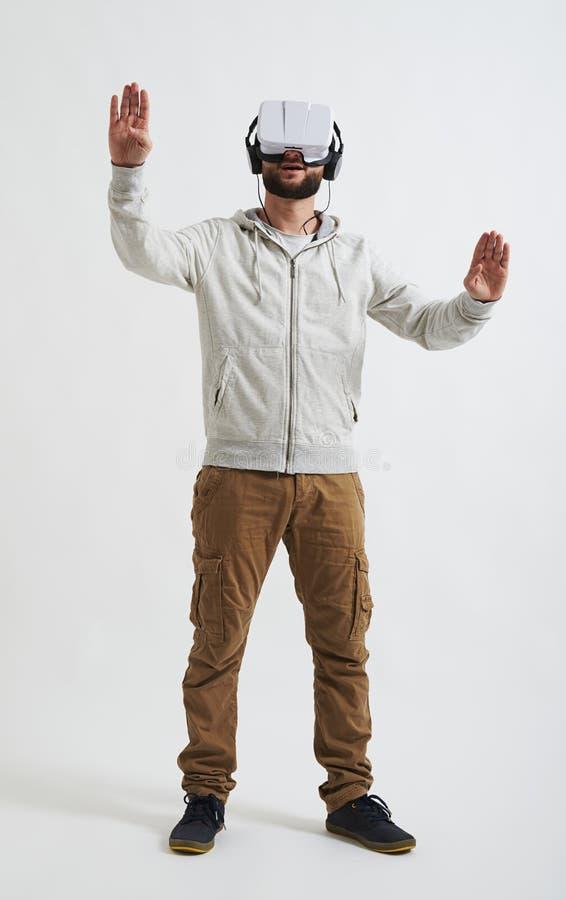 Ung man som försöker att skjuta något bärande virtuell verklighetexponeringsglas arkivbilder