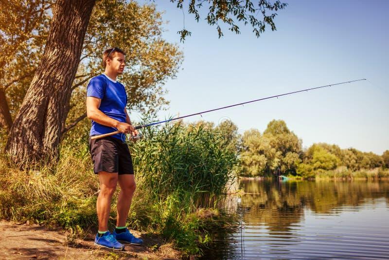 Ung man som fiskar på flodbanken Fiskare som tycker om hobby rotering royaltyfri foto
