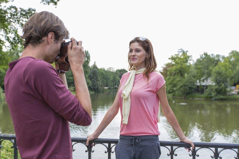 Ung man som fotograferar kvinnan på lakesiden royaltyfria bilder