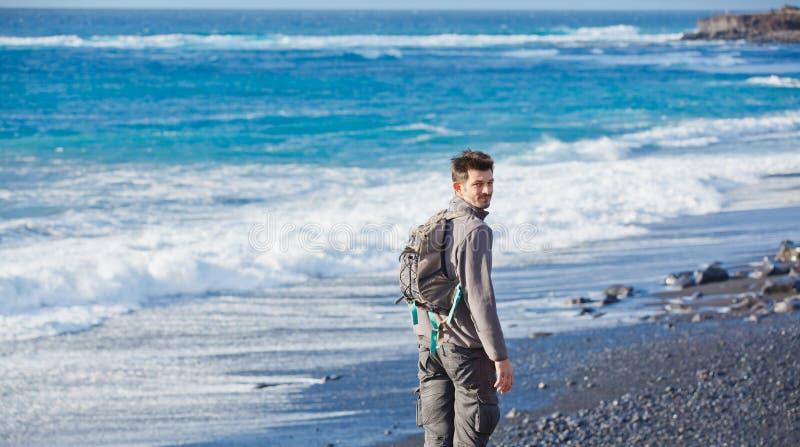 Ung man som fotvandrar nära havet royaltyfri fotografi