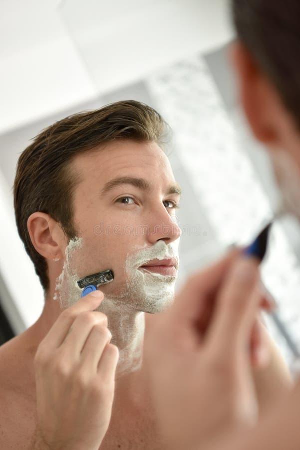 Ung man som framme rakar av spegeln royaltyfria bilder