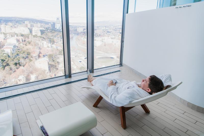 Ung man som framme vilar på modern solstol av det stora fönstret med stadssikt i modern brunnsort arkivbilder