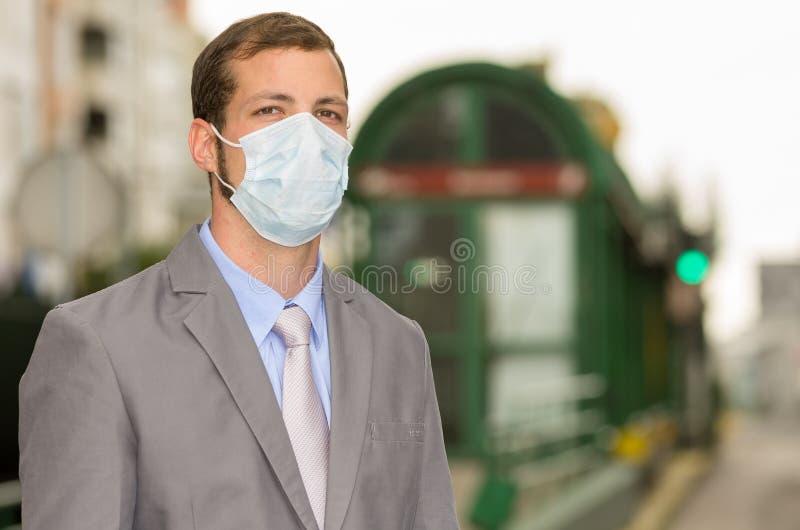 Ung man som går bära en maskering i stadsgata arkivfoto