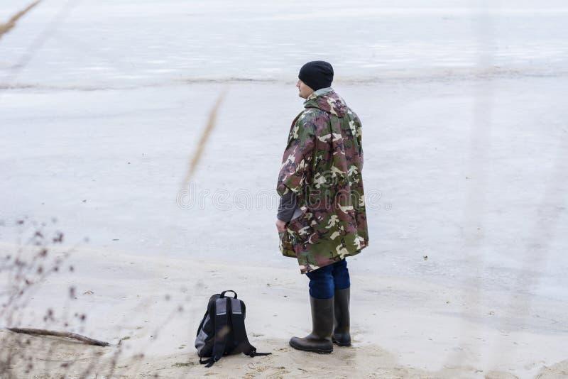 Ung man som går på stranden som håller ögonen på det djupfrysta vattnet i ett militärt regnlag fotografering för bildbyråer