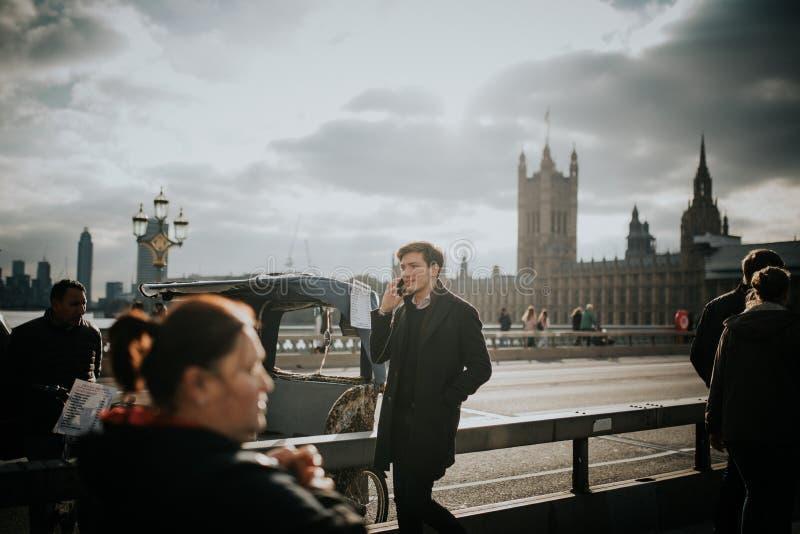 Ung man som går vid den Westminster brotrottoaren, medan stanna till telefonen, med den Westminster slotten i bakgrunden, i Londo arkivfoton
