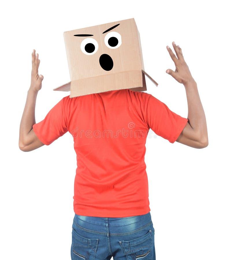 Ung man som gör en gest med en kartong på hans huvud med ledsen fa arkivfoto