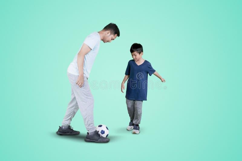 Ung man som gör fotbollövningar med hans son royaltyfria foton