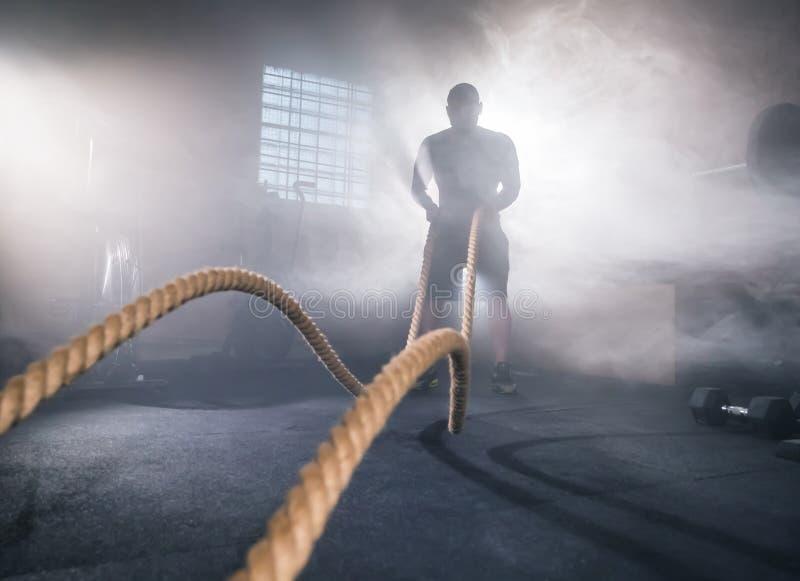 Ung man som gör hård övningsgenomkörare i idrottshall royaltyfri fotografi