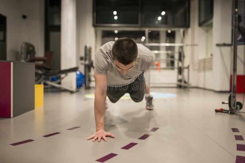 Ung man som gör push-UPS i idrottshallen fotografering för bildbyråer