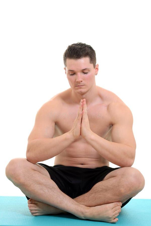 Ung man som gör yoga arkivfoto