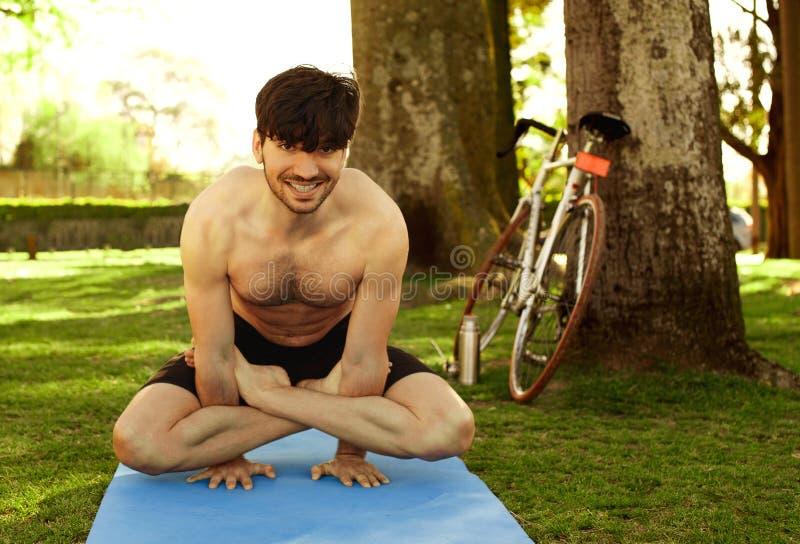 Ung man som gör yogaställing i gräset royaltyfri foto