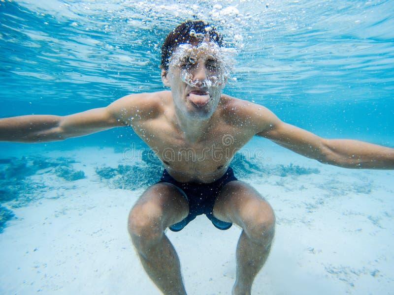 Ung man som g?r grimaser undervattens- bl?tt klart vatten royaltyfri foto
