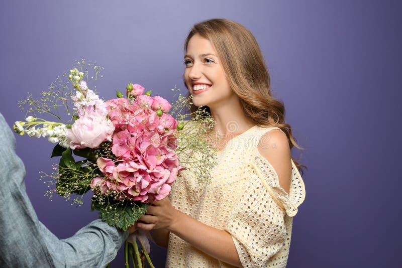 Ung man som ger härliga blommor till hans älskade flickvän på färgbakgrund royaltyfri foto