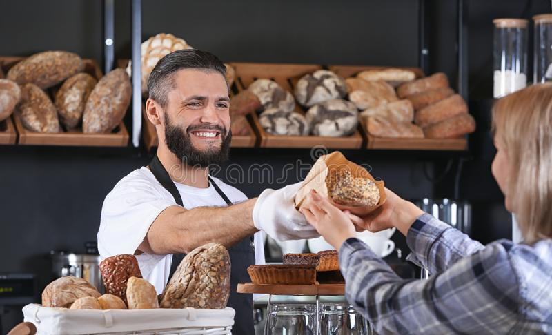 Ung man som ger nytt bröd till kvinnan i bageri royaltyfri foto