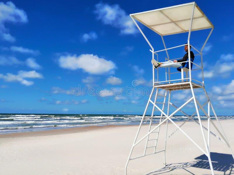 Ung man som håller ögonen på havskusten från ett räddningsaktiontorn mot den blåa himlen arkivbild