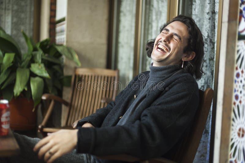 Ung man som hårt skrattar på en terrass arkivbild