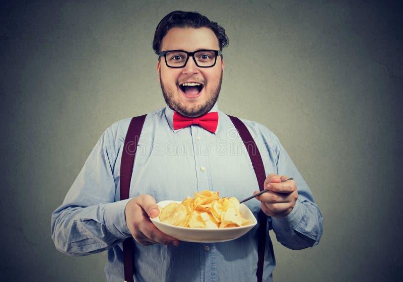 Ung man som har en platta av potatischiper royaltyfria bilder