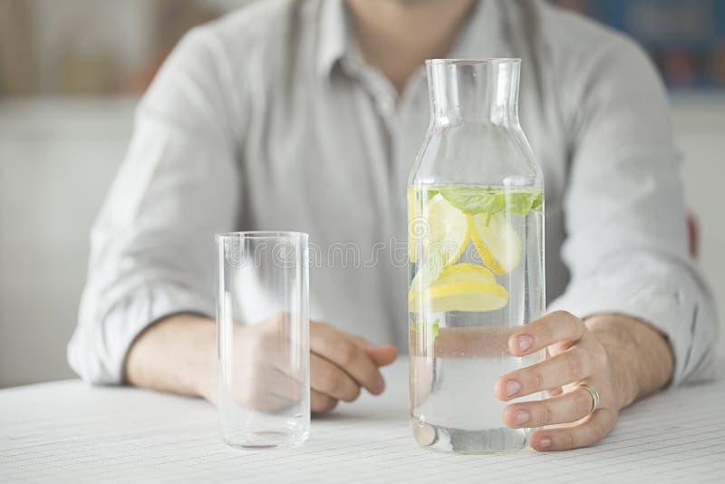 Ung man som har flaskan av vatten och exponeringsglas i kök arkivbilder
