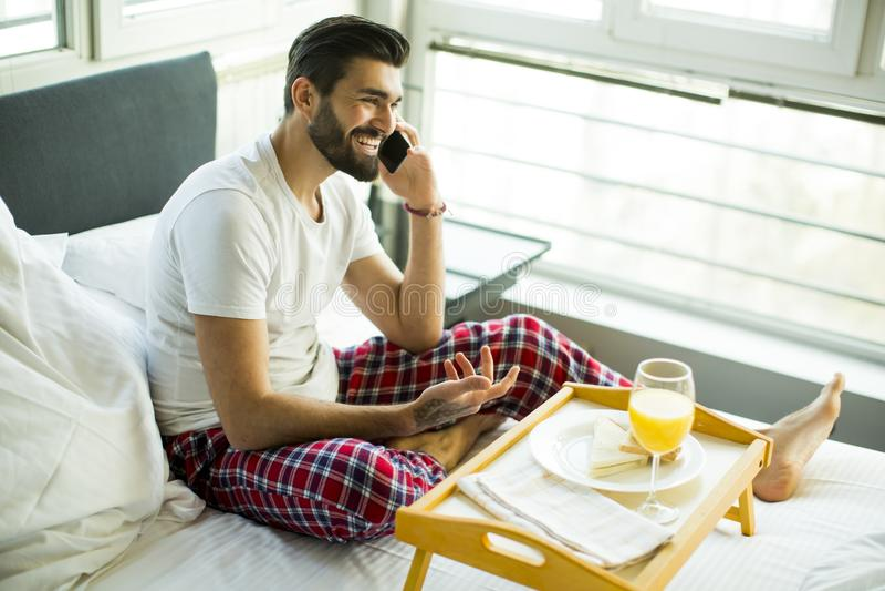 Ung man som har frukosten i säng och använder en mobiltelefon royaltyfri foto