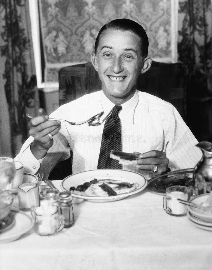 Ung man som har frukosten, och le (alla visade personer inte är längre uppehälle, och inget gods finns Leverantörgarantier det arkivbild