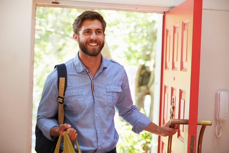 Ung man som hem går tillbaka för arbete med shopping royaltyfria foton