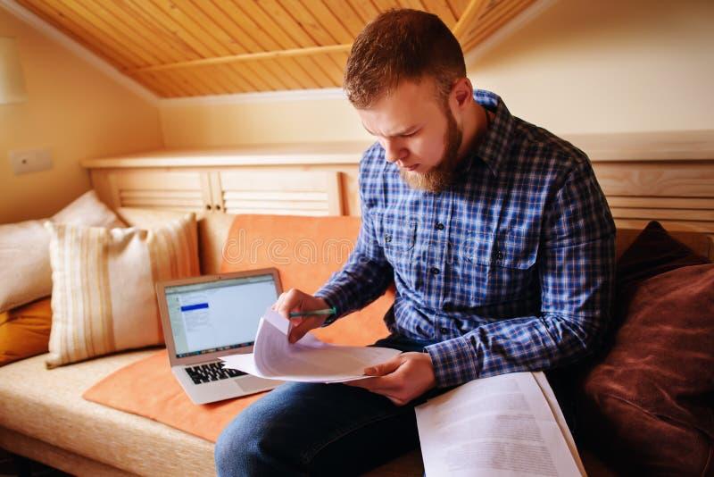 Ung man som hemifrån studerar att sitta på dokument för ett soffainnehav, medan arbeta på en bärbar datordator arkivbild