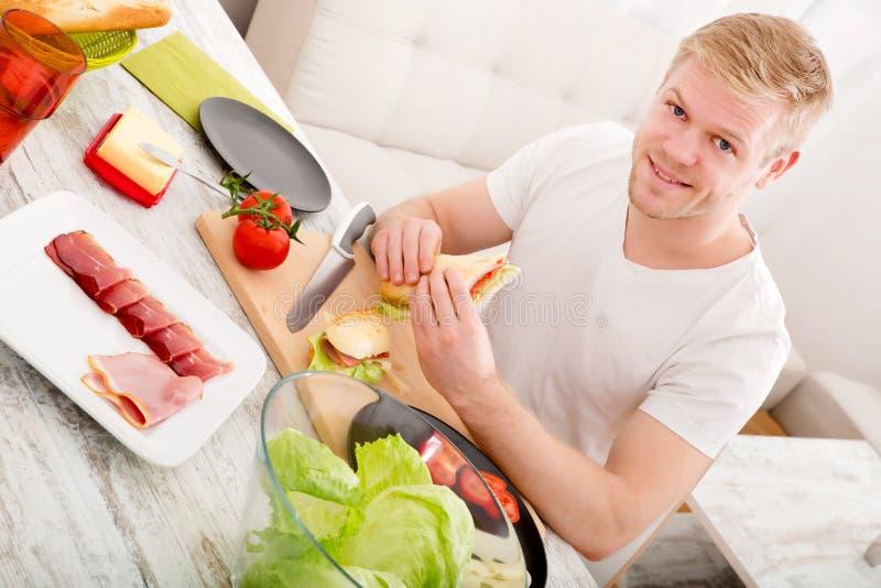 Ung man som hemma äter en smörgås fotografering för bildbyråer