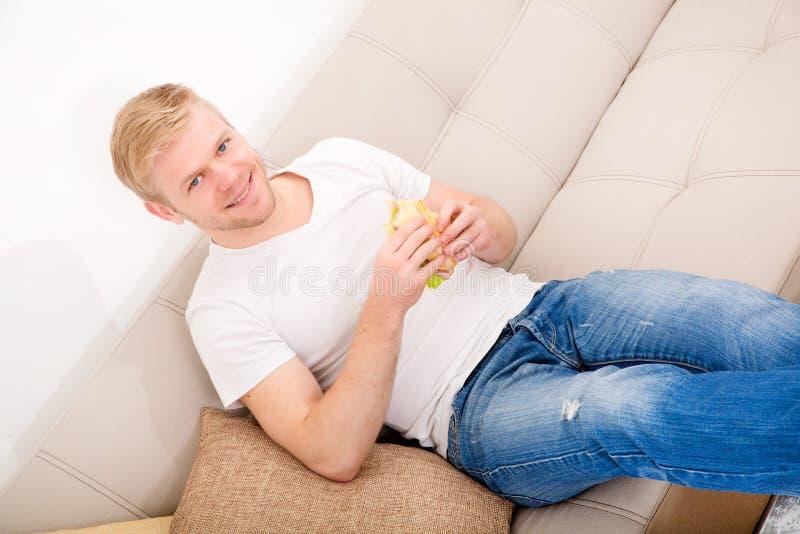 Ung man som hemma äter en smörgås royaltyfria foton