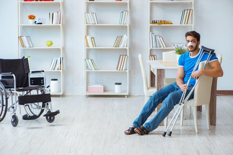 Ung man som hemma återställer efter kirurgi med kryckor och en w arkivbild