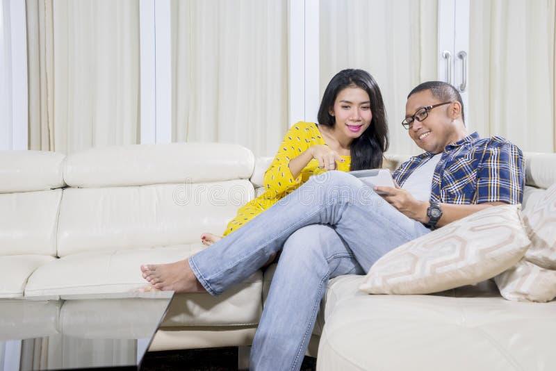Ung man som hemma använder en minnestavla med hans fru royaltyfria foton