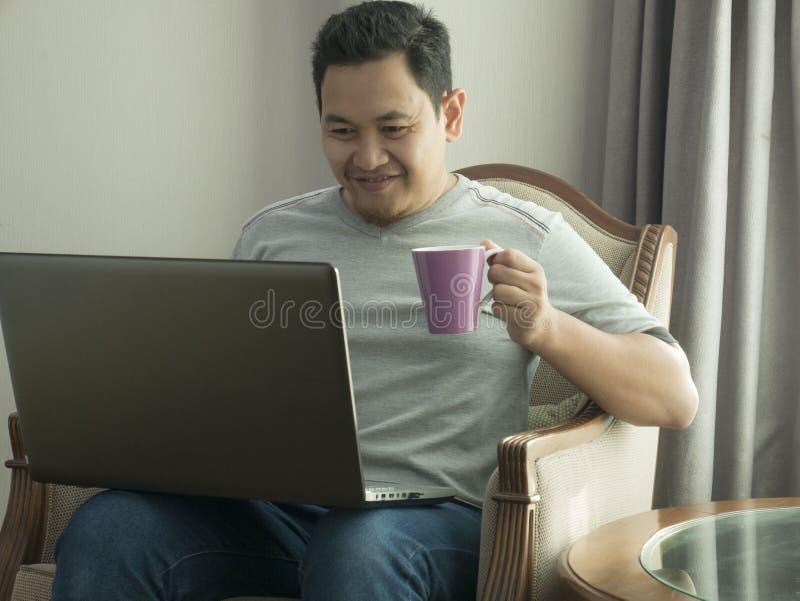 Ung man som hemma arbetar på hans bärbar dator som ler uttryck arkivfoto