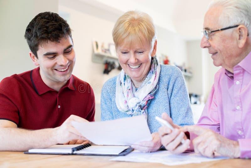 Ung man som hemma hjälper höga par med finansiell skrivbordsarbete royaltyfri bild