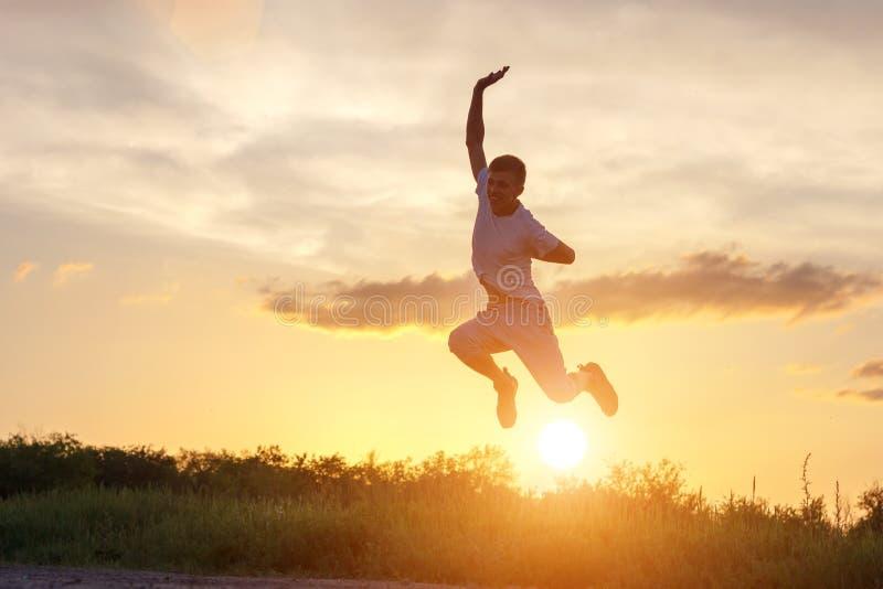 Ung man som hoppar upp mot solnedgånghimlen arkivfoton