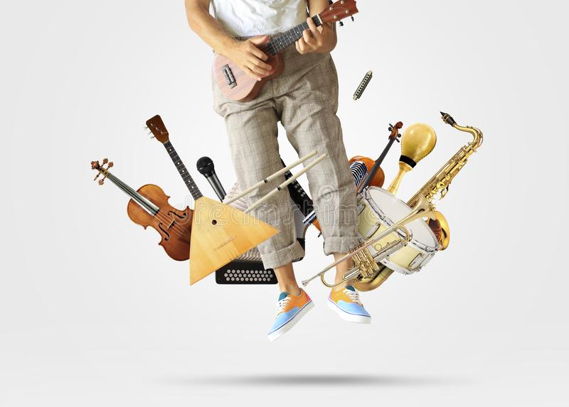 Ung man som hoppas upp att spela gitarren arkivfoto