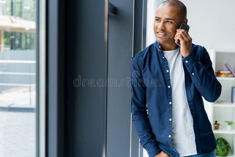 Ung man som i regeringsställning talar på hans mobiltelefon Afrikanskt utövande sammanträde på hans skrivbord med bärbara datorn royaltyfria bilder